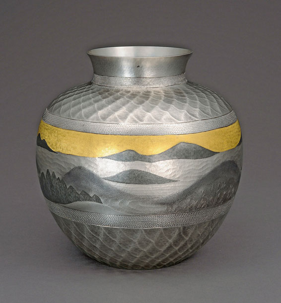 An ornamental metal vase with hammered details depicting a natural scene, done via tankin.