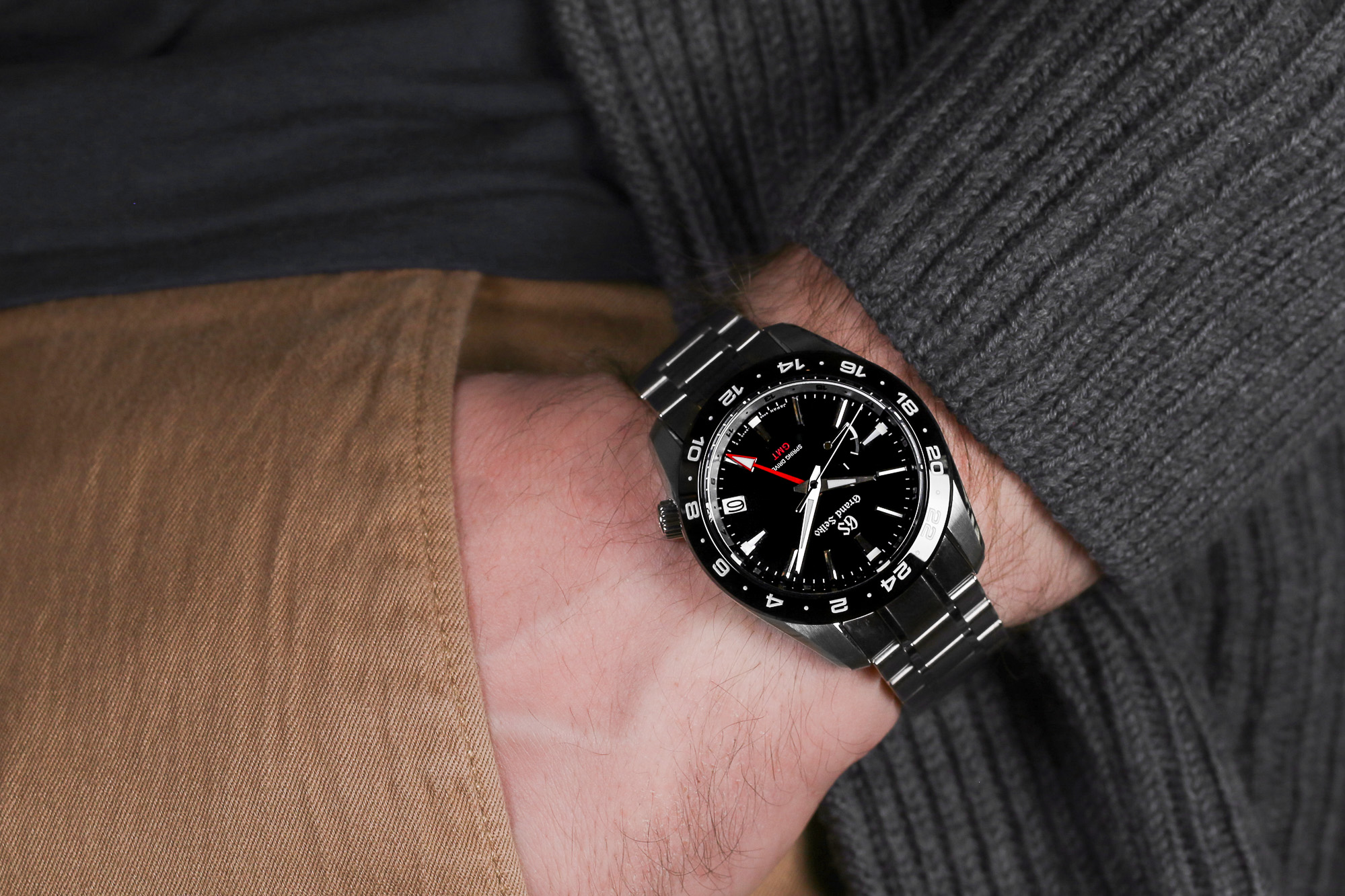 Grand Seiko SBGE253 black dial watch with red accents on the wrist.