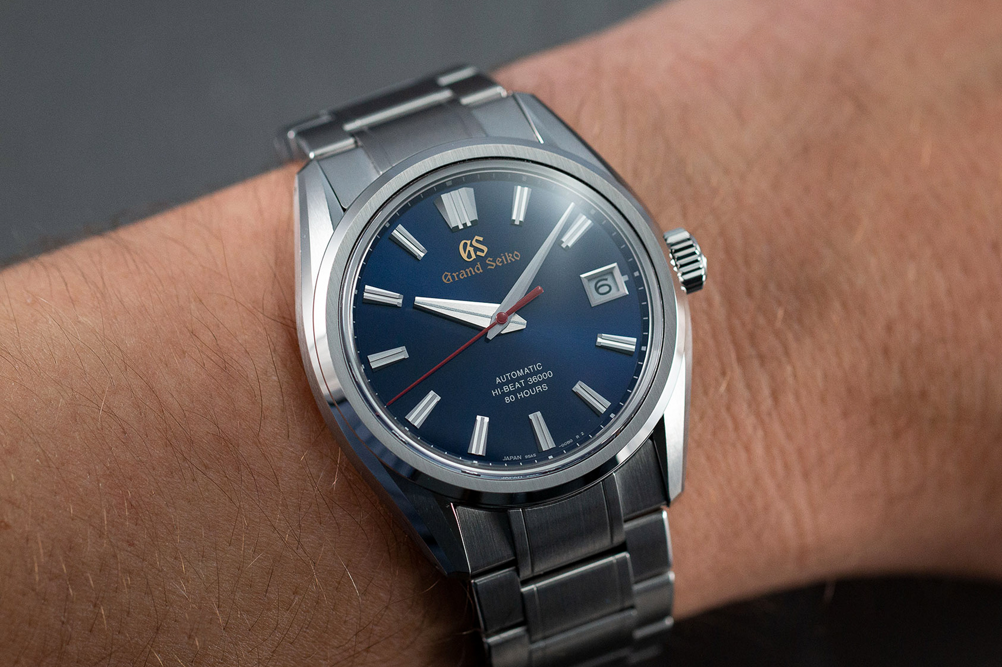 Grand Seiko SLGH003 blue dial stainless steel wristwatch on a wrist.