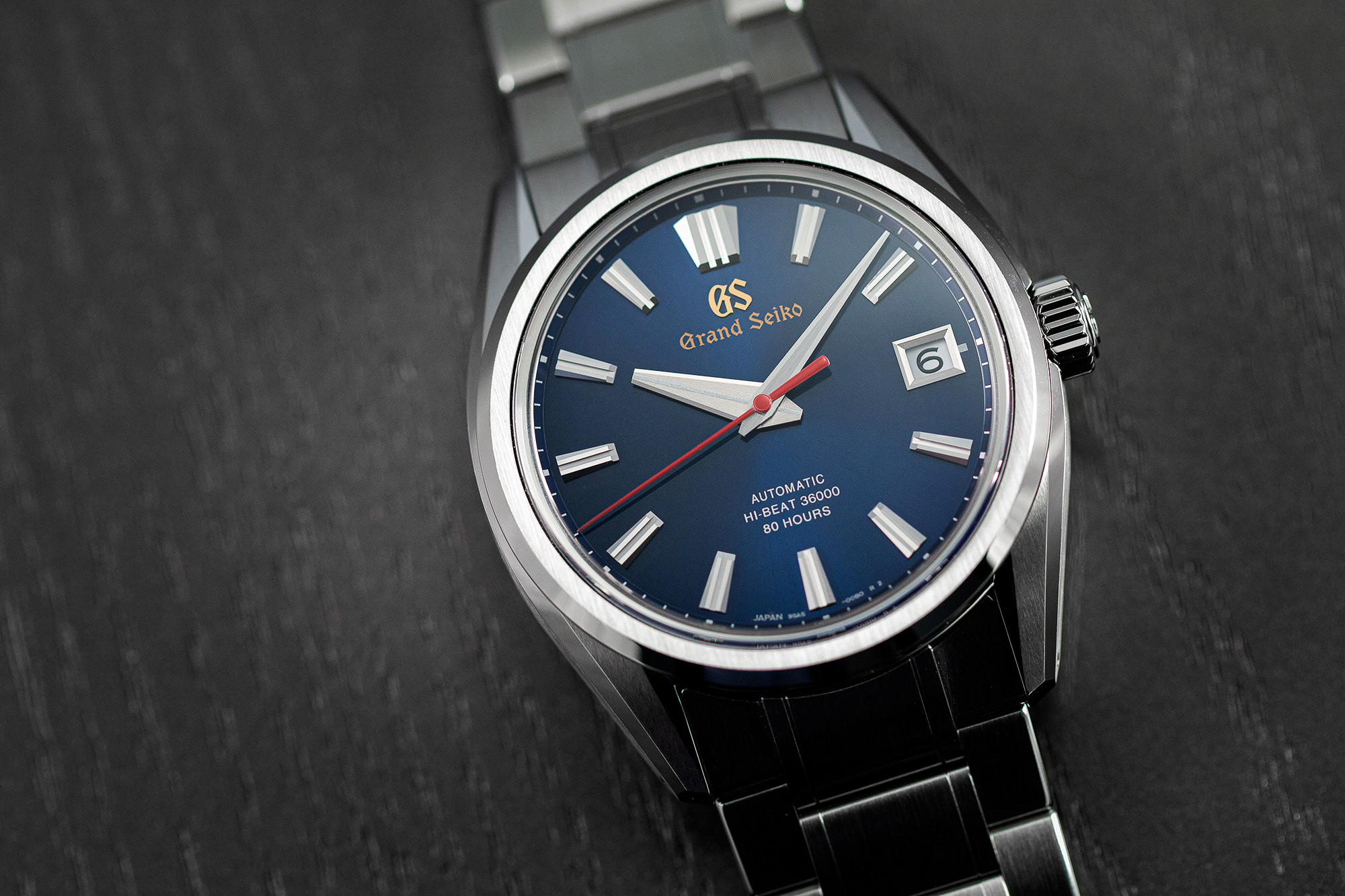 Grand Seiko SLGH003 wristwatch with a blue dial and red accents on a tabletop.