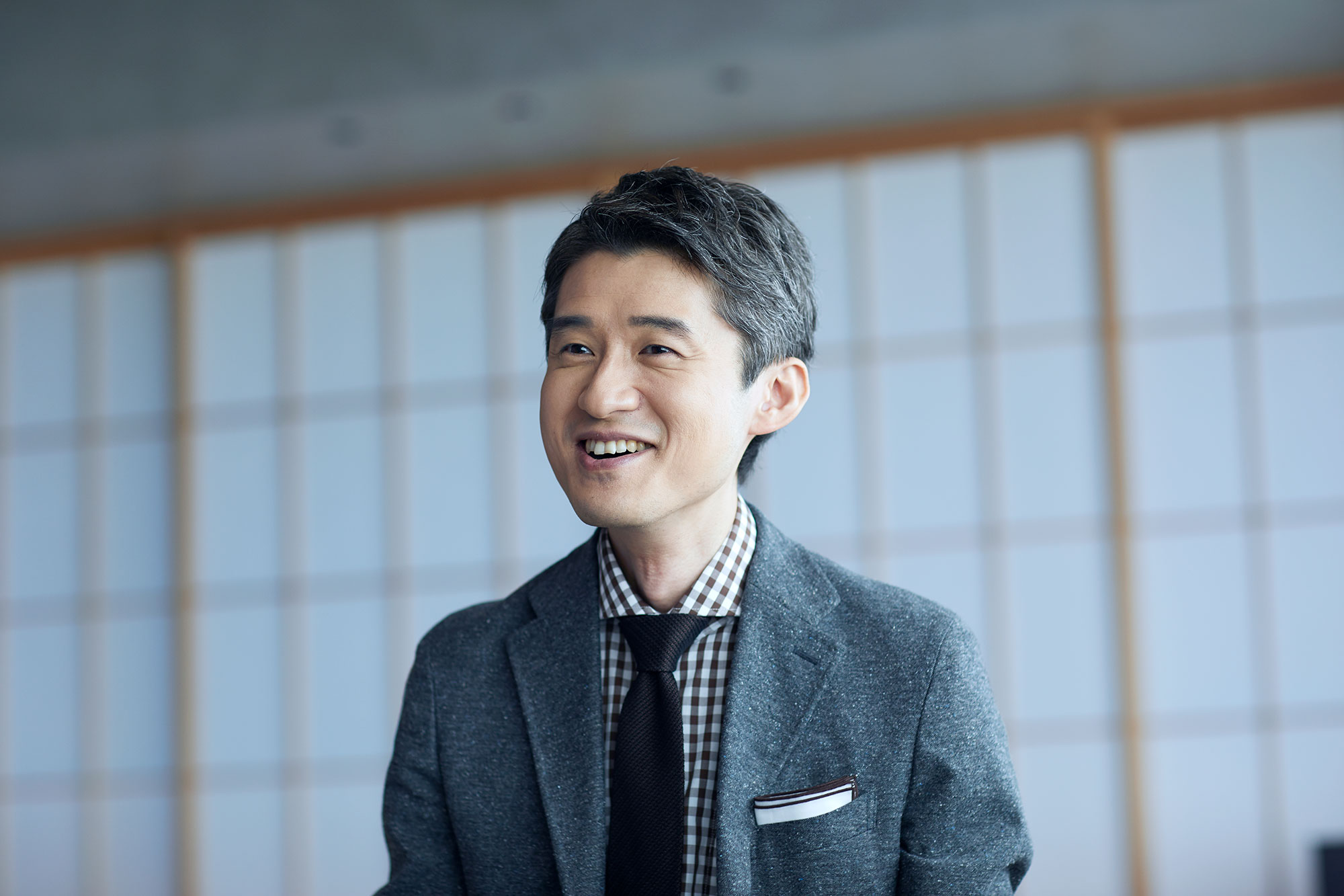 Hishashi Fujieda in a grey suit, gingham shirt, and black tie.