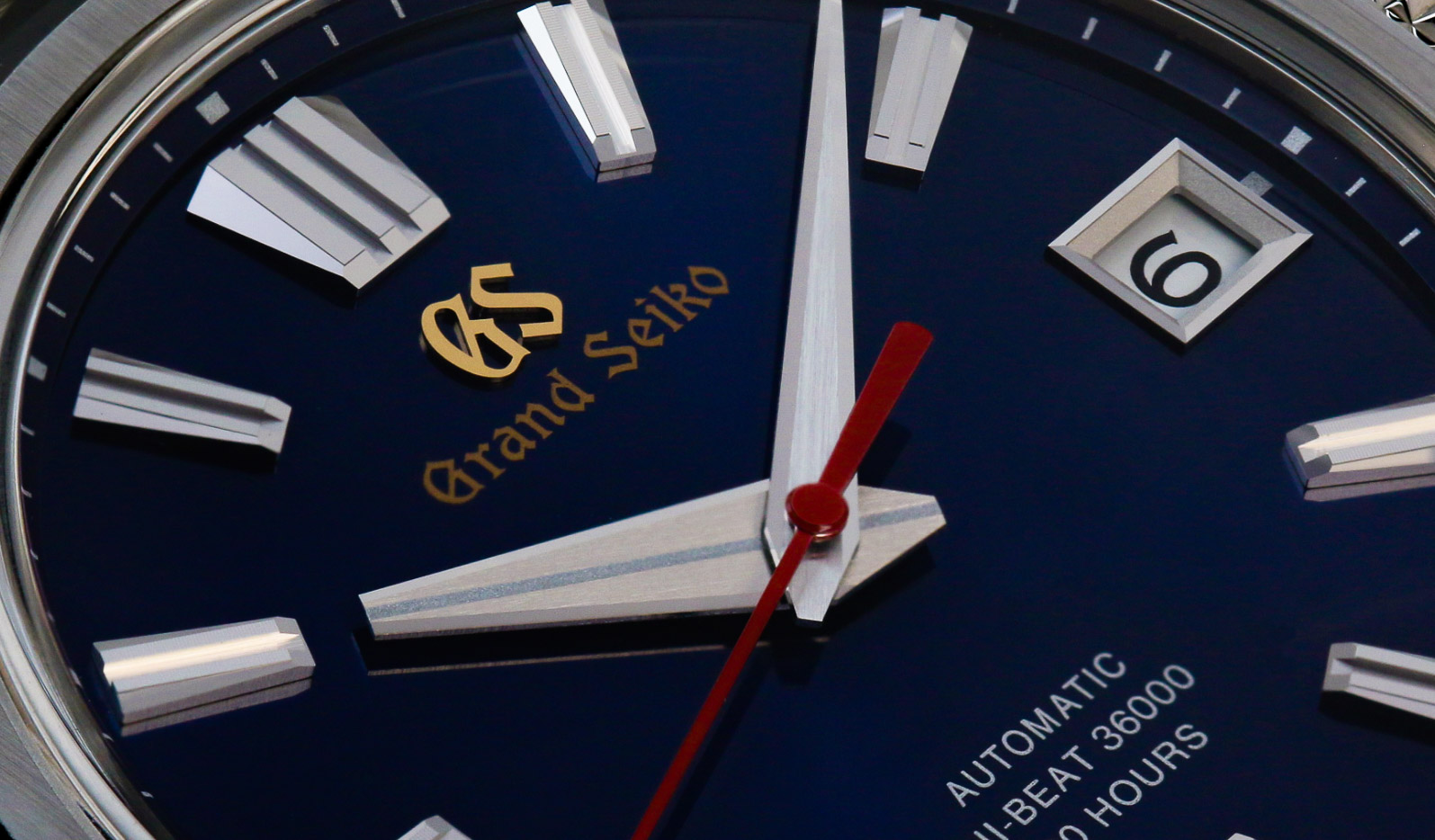 Close up of Grand Seiko SLGH003 blue dial with red and golden accents.