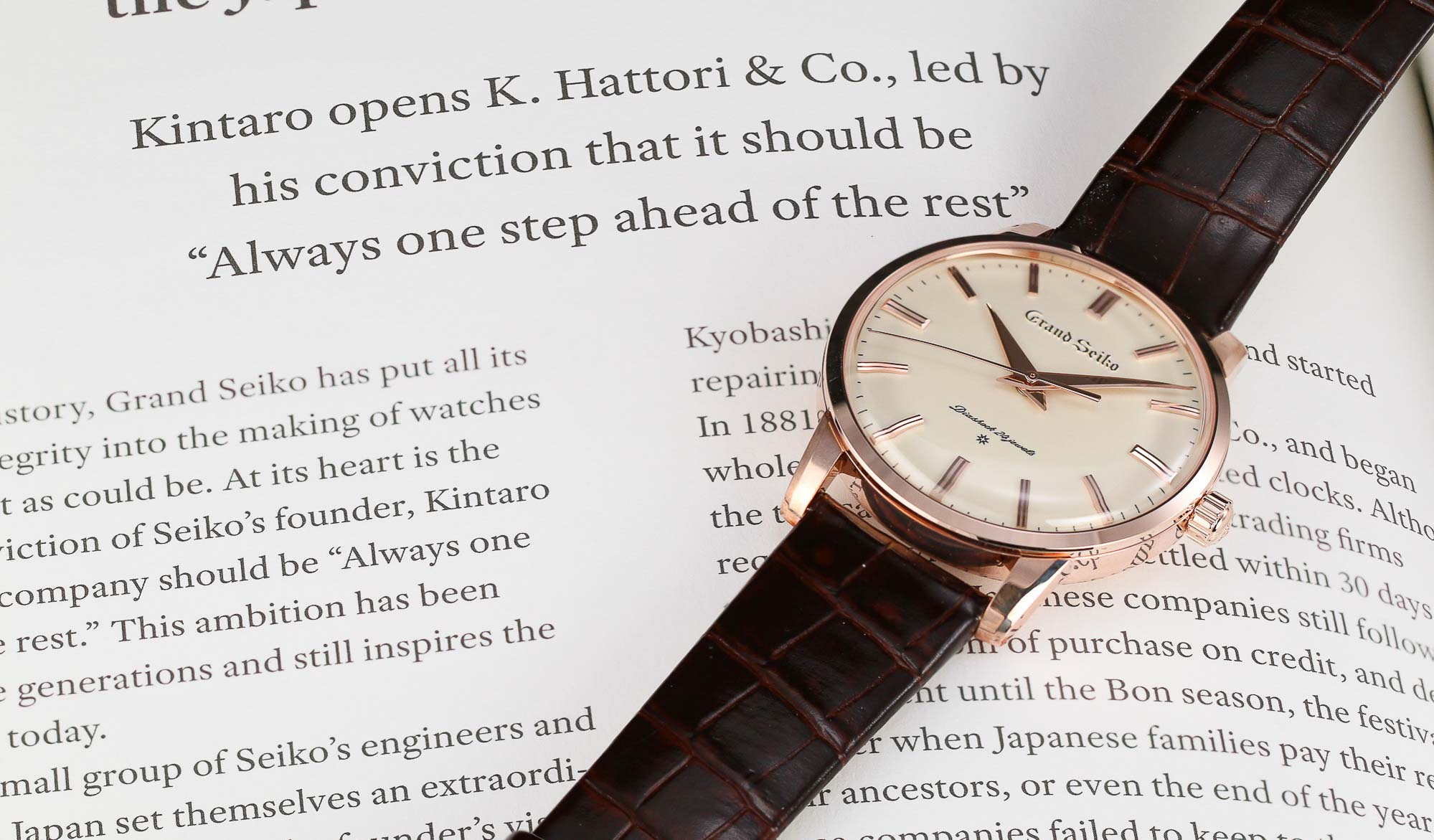 Grand Seiko SBGW260 golden dress watch laying on a book.