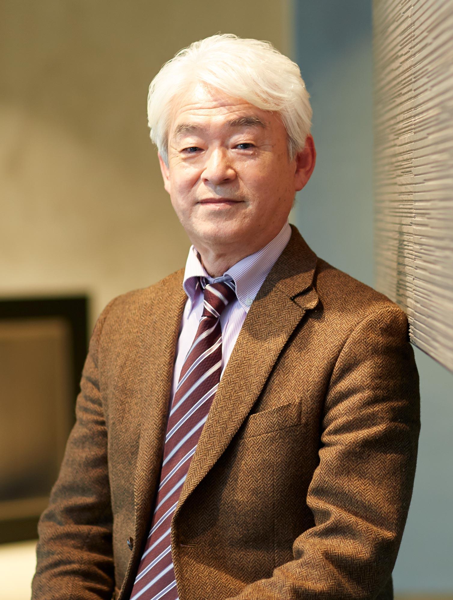 Portrait of Nobuhiro Kosugi wearing a brown tweed suit.
