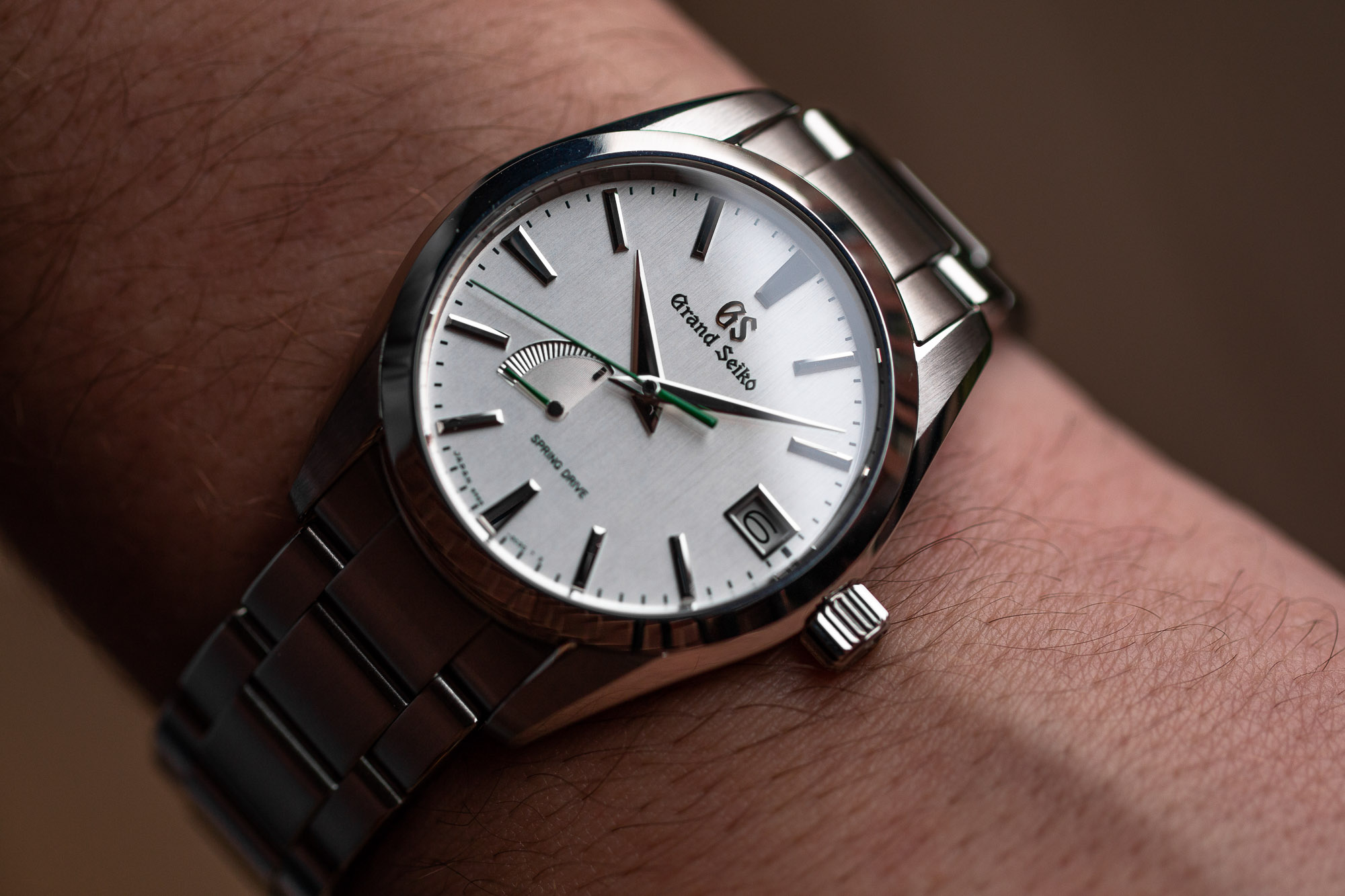 Light dial Grand Seiko SBGA427 on the wrist.