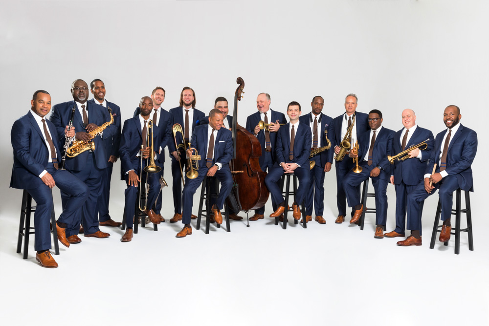 Jazz at Lincoln Center members wearing blue suits and holding instruments