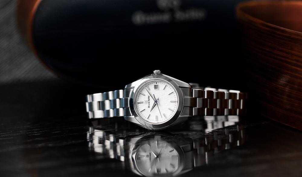 Grand Seiko STGF359 white dial wristwatch on a tabletop.