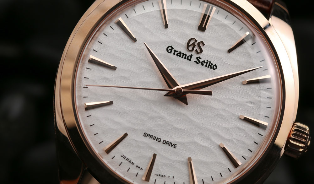 Dial closeup of Grand Seiko SBGY008 18k gold watch.